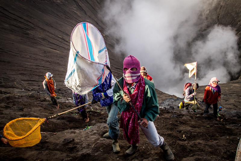 Every year the Tenggerese people who live in the villages around Mount Bromo gather to pay tribute to the god of the volcano in a festival known as Yadnya Kasada. They carry offerings up the volcano to throw into the crater. Some people however chose to risk their lives and climb onto the steep inner slope of the crater with nets. They run and jump to try and catch the offerings before they reach the choking heart of the volcano. The belief is that each item they catch is a blessing from the god of the volcano. This young man had covered his face to protect his identity from those throwing the offerings and to reduce the impact from the toxic volcanic gasses. #BBC #EarthOnLocation #Bromo #Kasada #Festival #Indonesia #Volcano #Offering #Java