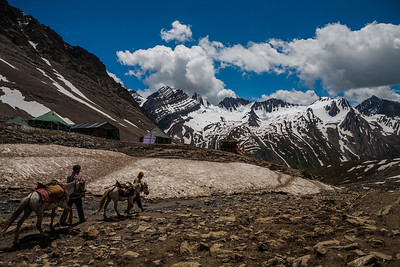 Two horsemen and their horses walk through the waters of the melting glaciers in the backdrop of black and white mountains towards the Mahaganus top, the highest point of the Amarnath yatra route via Pahalgam at nearly 4200 meters.