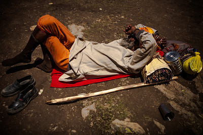 A sadhu sleeps on the ground with all his belongings close by after crossing the Mahaganus top, the highest point of the Amarnath yatra.