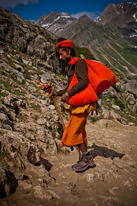 A sadhu with all his baggage wrapped in orange cloth and the holy walking stick on the Amarnath yatra