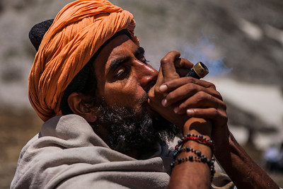 A sadhu takes a break with his smoking pipe on the way to the holy cave at Amarnath in Kashmir, India.