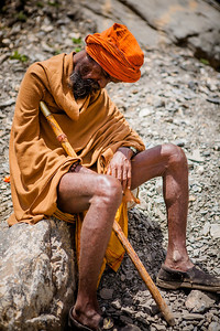 A sadhu, dressed in minimum clothing and battered shoes falls asleep as he sits to rest on a rock, his heavy walking stick still in his hand on a steep stretch of Pissutop, the first mountain peak of Amarnath yatra.