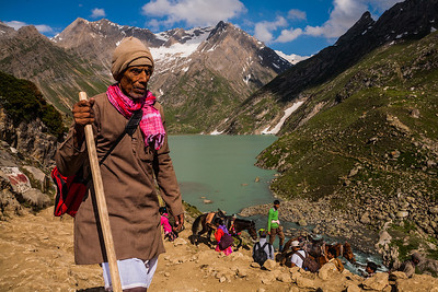 Old man wearing a simple kurta, carrying his bag across his chest and a wooden walking stick braves the rough terrain and the cold weather at Sheshnag on his Amarnath yatra.