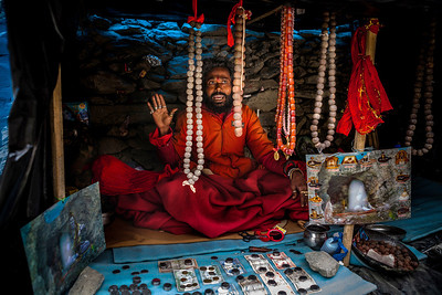 A bearded man posing as a sadhu, dressed in a warm orange jacket and a red blanket, wearing several rings in his fingers sits in a small cave around the holy Amarnath cave trying to sell photos of the shivling, rudrakshas as well as some currency.