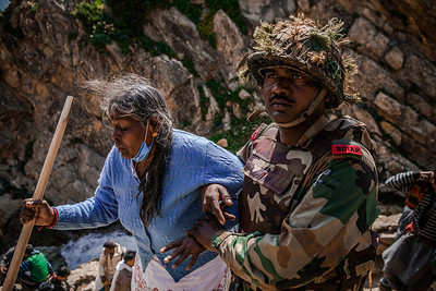 An Indian Army officer helps an old woman get through the final steep stretch to Pishutop, the first peak of the Amarnath yatra.