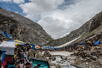 A sea of horses, shops and people in the midst of the snow and the mountains is the landscape around the opening of the holy Amarnath cave.