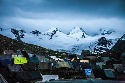The campsite at Sheshnag, the first night halt on the Amarnath yatra route via Pahalgam with several tents spread out as seen at the break of dawn with fresh snow from the previous night in the backdrop.
