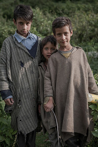 "Three young boys dressed in torn woolen traditional overcoats called ""firan"" at Chatpal a virgin region of Kashmir."