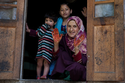 A woman from Thimran village in rural Kashmir with her daughters peeping through the window of her house displaying henna on her hands.