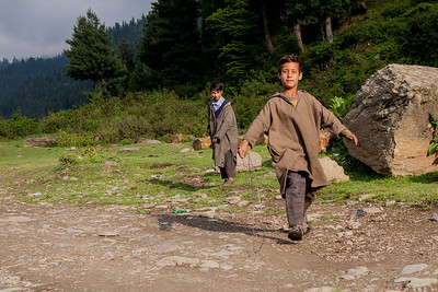 Two young boys wearing a traditional overcoat from Kashmir called firan play with a metal ring in the open grounds surrounded by pine trees at Chatpal in Kashmir