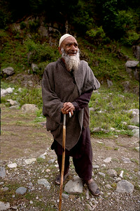 An old shepherd man with a beard takes a break and rests with the support of his walking stick on his way home with his flock in Chatpal, Kashmir