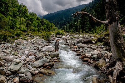 A man dressed in firan, the traditional overcoat from Kashmir stands on the rocks by a stream surrounded by a pine forest in Chatpal a virgin region in Kashmir.