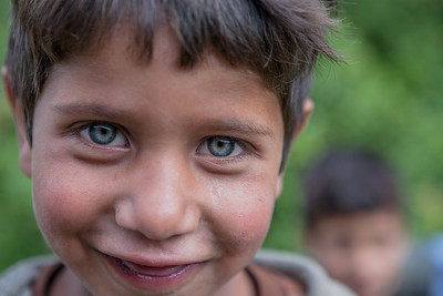 Portrait of an adorable young boy with green eyes and an innocent smile in Chatpal, Kashmir.