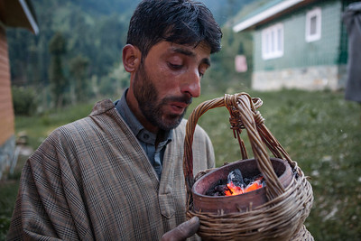 A man from Kashmir wears a traditional woolen coat called firan and fires up a charcoal fired handheld cane basket to keep warm.