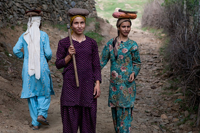 Two women carrying sickles head to the farms to cut some firewood in Lolab valley, Kupwara district in northern Kashmir, India