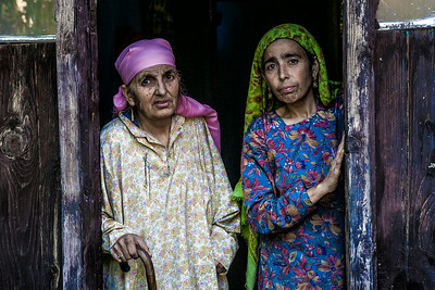 Two old women dressed in traditional Kashmir attire curiously peek out of their windows in Lolab valley, Kupwara district in northern Kashmir, India.