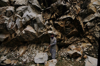 A man uses his spade to cut the rocks to smaller stones to be used in repairing the national highway NH1-B, a road leading to Sinthan Top in Kashmir.