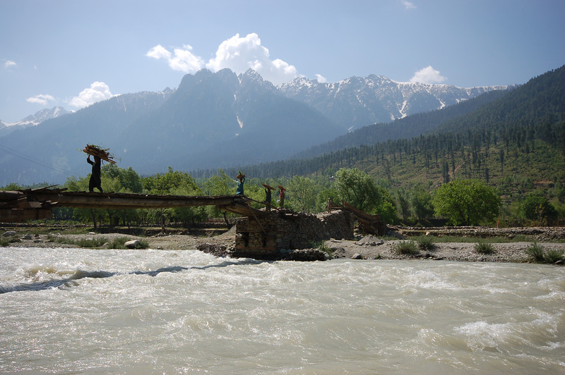 Locals precariously carry wood over the river in the Kashmir Valley.