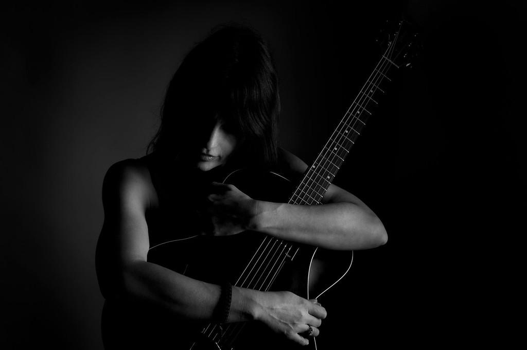 Hugging her guitar