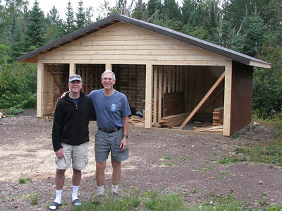Luke and Bob in Front of sided woodshed