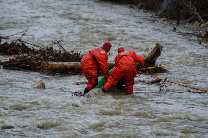 DAVID LACHANCE — BENNINGTON BANNER<br /> Members of the North Bennington Cold Water Support Team wade into the rain-swollen Roaring Branch of the Walloomsac River on Monday to retrieve a kayak. The kayak's owner was found safe, out of the water. Emergency crews responded around 4:30 p.m. when the kayak was spotted near the Park Street bridge.