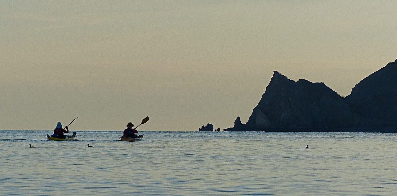 "Paddling toward Punta Bluff (also called Punta Refugio). Another example of how simple kayaking is without wind. The most important skill to learn in sea kayaking is ""Quickly get off the water when the wind starts to blow""."