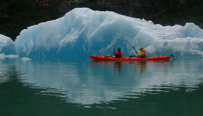 Red kayak in front of white iceberg. A guaranteed nice photo.