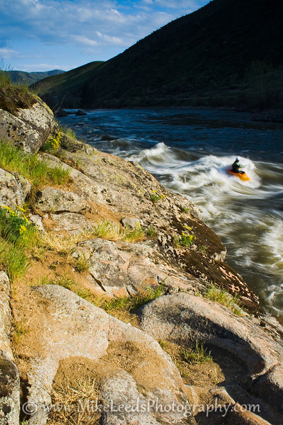 Paddler Matt Elam surfing as the sun goes down behind the mountains. Trimax wave on the Main Payette River in Idaho.