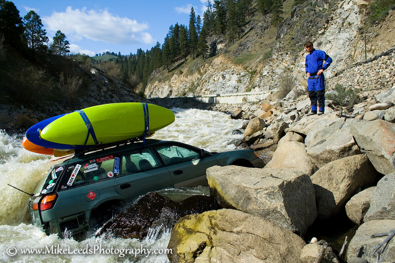 """My friend Brent trying to figure out how he is going to get his boat that is about to fall in.  Juicer Rapid on the North Fork Payette River in Idaho.  This photo has also been featured in """"Paddler Magazine"""".  July/August 08."""