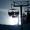 Winter Park, CO:  A group of skiers ride the chairlift to the top of mountain on clear cold day.
