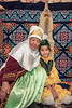 Grandmother and granddaughter inside a yurt with hanging foxskin, Almaty, Kazakhstand