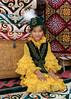 Kazaky girl in a beautiful yellow dress inside a traditional yurt, Almaty, Kazakhstan