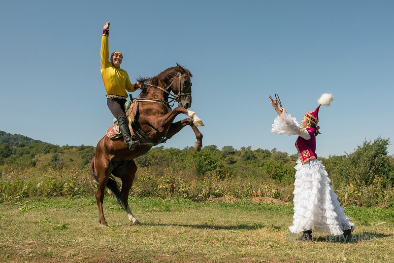 Kazakh man and woman teaming up with rearing horse, Almaty Kazakhstan