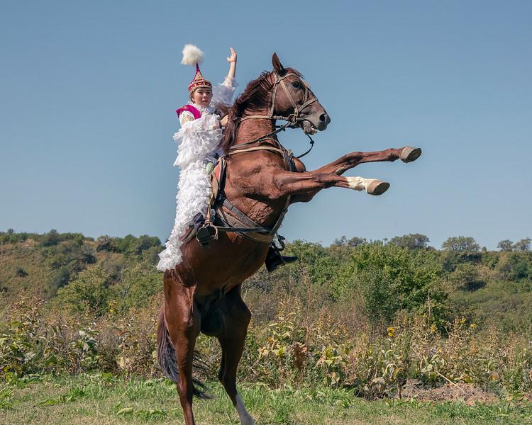 Kazakh woman in traditional attire mounted on a rearing horse, Almaty, Kazakhstan