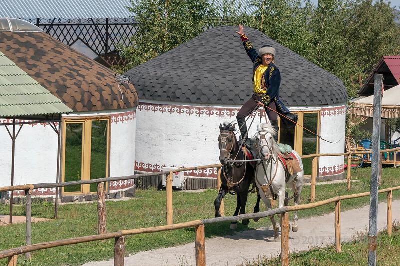 Kazakh trick rider on two horses, riding by yurts, Alamty, Kazakhstan