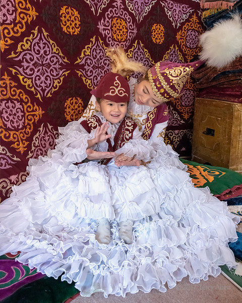 Kazakh mother and daughter in traditional attire in a yurt, playing pattycake, Almaty, Kazakhstan