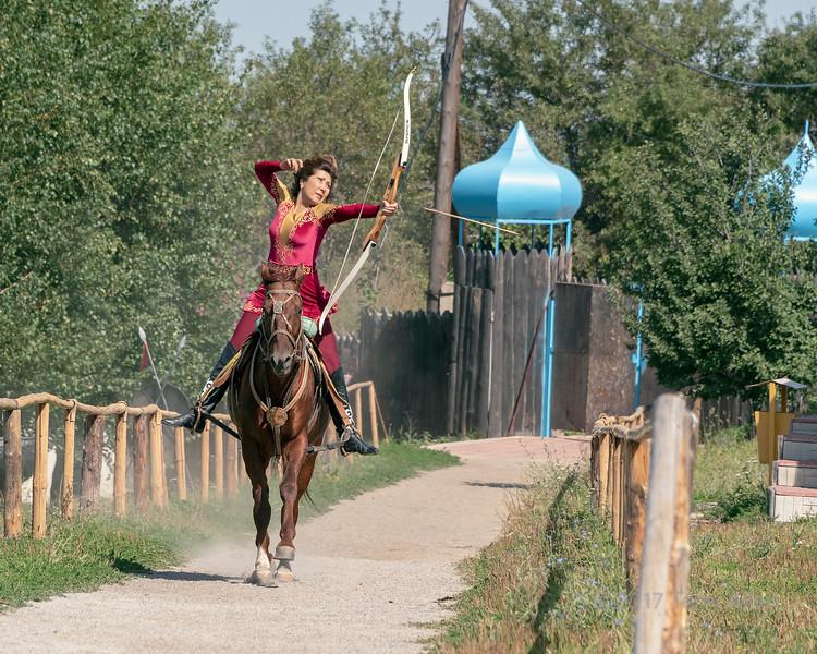 Kazakh woman on horseback shooting arrow from bow, Almaty, Kazakhstan