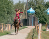 Kazakh woman on horseback shooting arrow from bow, Almaty, Kazakhstan