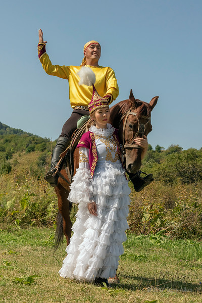 Kazakh man and woman in traditional attire with horse, Almaty, Kazakhstan