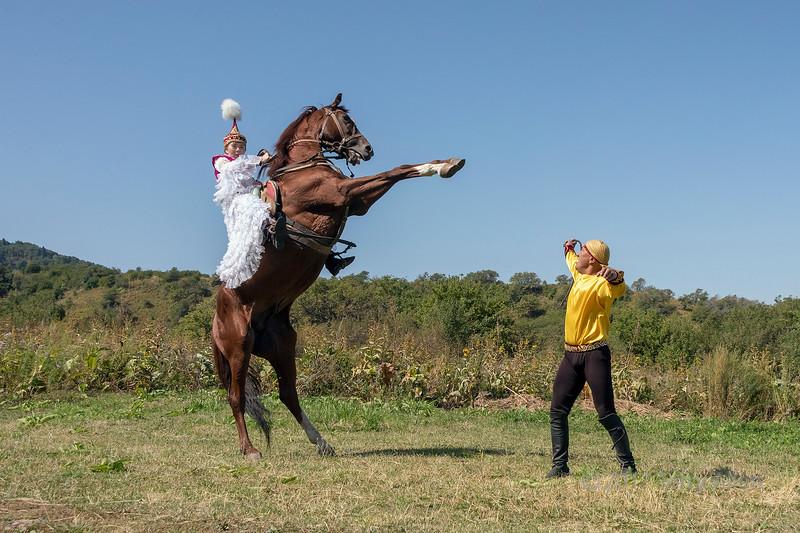 Kazakh woman in traditional attire on a rearing horse, Almaty, Kazakhstan