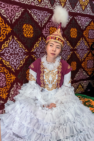 Kazakh woman in traditional attire sitting in a yurt, Alamty, Kazakhstan