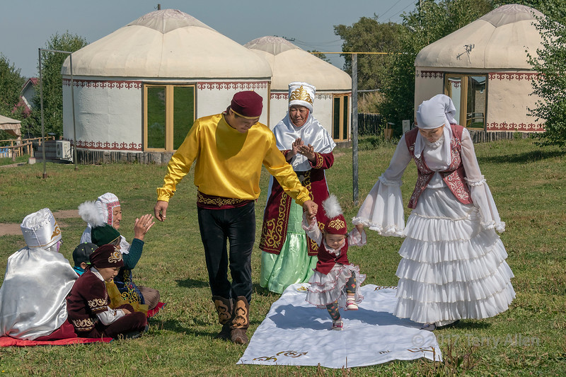 High stepping 'Tusau Kesu' ceremony (cutting the rope) enthusiastic child with family in festive attire, Almaty, Kazakhstan