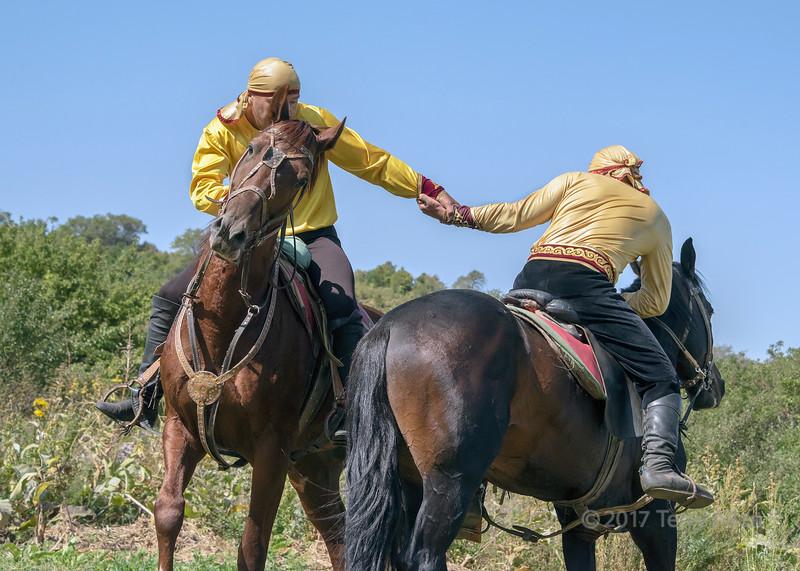 Kazakh men in tradiitoinal attire demonstrate the sport of horseback wrestling, Almaty, Kazakhstan