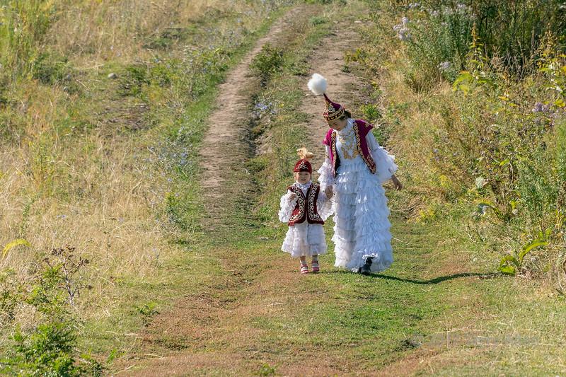 Mother and daughter in festive attire walking downhill, Almaty, Kazakhstan