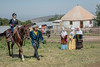 Kazakh mother and grandmothers watch a young boy learning to ride a horse, Almaty, Kazakhstan