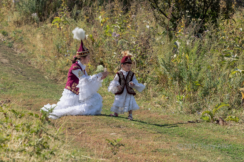Colecting wildflowers, mother and daughter in festive attire, Almaty, Kazakhstan