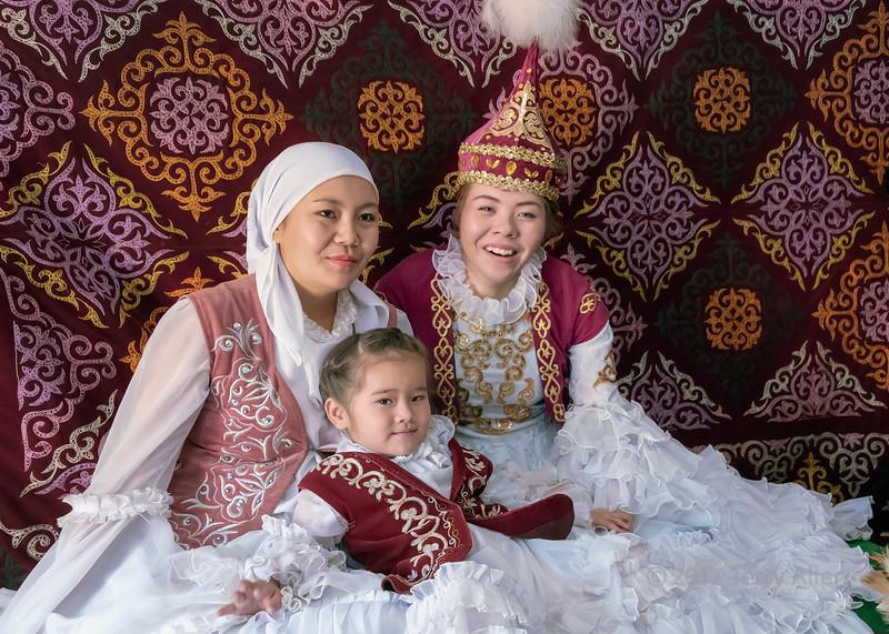 Three generations of happy women in traditional attire in a yurt, Almaty, Kazakhstan
