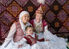 Three generations of happy women in traditional attire in a yurt, Almaty, Kazakhstan