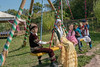 Group of children in festive attire on a swing, Almaty, Kazakhstan