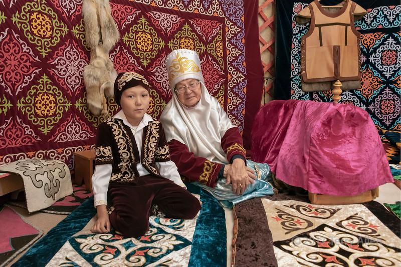 Grandmother and grandson in traditional attire inside a yurt, Almaty, Kazakhstan